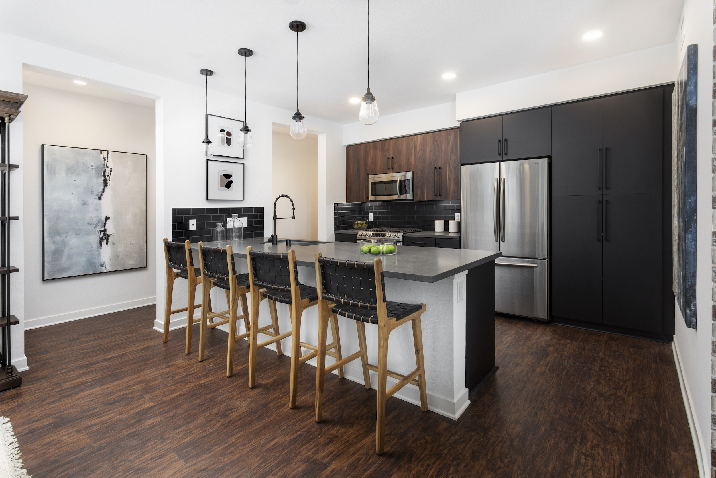 Artistry modern kitchen with black cabinetry and stainless steel appliances at Broadstone Archive Apartments